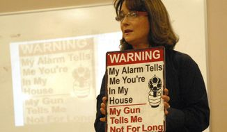 Alaska Rep. Lora Reinbold, R-Eagle River, holds a sign warning prowlers against entering her home during a public meeting on public safety held Saturday, Jan. 6, 2018 at the Eagle River Town Center building in Eagle River, Alaska. Armed and angry, Chugiak-Eagle River residents say it's time to get tough on crime.(Matt Tunseth/Chugiak Eagle River Star via AP)
