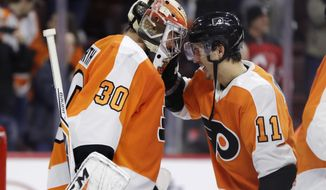 Philadelphia Flyers' Michal Neuvirth, left, and Travis Konecny celebrate after an NHL hockey game against the New Jersey Devils, Saturday, Jan. 20, 2018, in Philadelphia. Philadelphia won 3-1. (AP Photo/Matt Slocum)