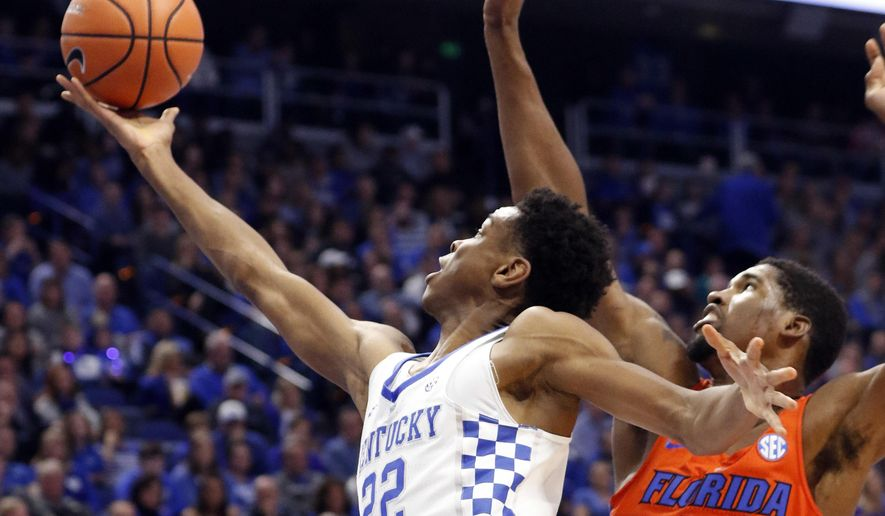 Kentucky's Shai Gilgeous-Alexander (22) shoots while pressured by Florida's Kevarrius Hayes (13) during the first half of an NCAA college basketball game, Saturday, Jan. 20, 2018, in Lexington, Ky. (AP Photo/James Crisp)