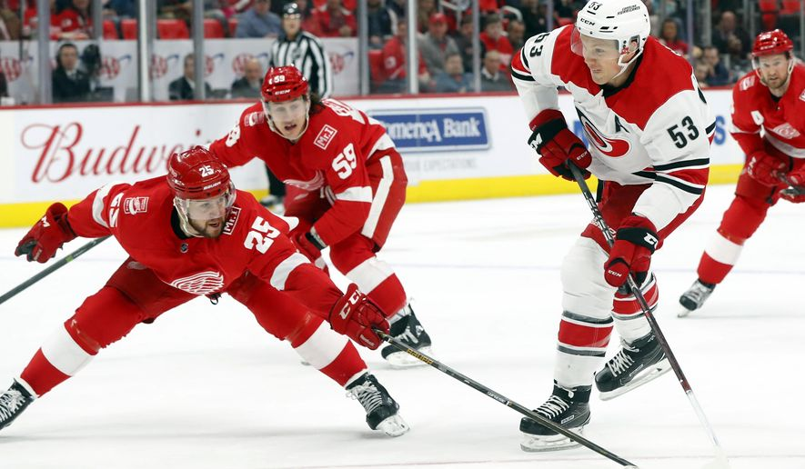 Detroit Red Wings defenseman Mike Green (25) pokes at a shot by Carolina Hurricanes left wing Jeff Skinner (53) in the first period of an NHL hockey game Saturday, Jan. 20, 2018, in Detroit. (AP Photo/Paul Sancya)