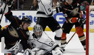 A shot by Anaheim Ducks center Adam Henrique, left, gets behind Los Angeles Kings goaltender Jonathan Quick (32) as defenseman Christian Folin (5), of Sweden, defends against right wing Corey Perry (10) during the second period of an NHL hockey game in Anaheim, Calif., Friday, Jan. 19, 2018. The puck stayed out of the goal. (AP Photo/Alex Gallardo)