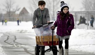 """In a Jan. 11, 2018 photo, Trey Munnerlyn and Kharisma Vreeland, students at Hellgate Elementary in Missoula, Mont., trek across the school campus making a delivery from one building to another as part of their jobs in the """"Hawks Helpers,"""" program. The school jobs program is meant to give students meaningful work that gives them responsibility and connects them to the school. Jobs are posted on a hall bulletin board and students have to apply and interview for the work. (AP/Missoulian/Kurt Wilson)/The Missoulian via AP)"""