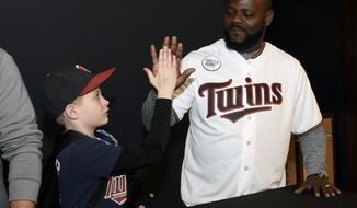 Minnesota Twins' Fernando Rodney, right, celebrates with a fan after giving a correct answer while playing a trivia game at the baseball team's TwinsFest, Friday, Jan. 19, 2018, in Minneapolis. (AP Photo/Hannah Foslien)
