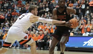 Southern California's Chimezie Metu (4) tries to get past Oregon State's Tres Tinkle (3) in the first half of an NCAA college basketball game in Corvallis, Ore., Saturday, Jan. 20, 2018. (AP Photo/Timothy J. Gonzalez)