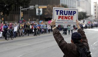 A supporter of President Donald Trump holds a sign as a women's march heading to the Texas State Capitol passes on the one-year anniversary of President Donald Trump's inauguration, Saturday, Jan. 20, 2018, in Austin, Texas. (AP Photo/Eric Gay)