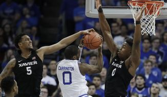 Xavier guard Trevon Bluiett, left, blocks a shot by Seton Hall guard Khadeen Carrington, center, during the first half of an NCAA college basketball game, Saturday, Jan. 20, 2018, in Newark, N.J. Xavier's Tyrique Jones (0) helps defend on the play. (AP Photo/Julio Cortez)