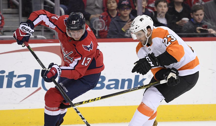 Philadelphia Flyers defenseman Brandon Manning (23) battles for the puck against Washington Capitals left wing Jakub Vrana (13), of Czech Republic, during the second period of an NHL hockey game, Sunday, Jan. 21, 2018, in Washington. (AP Photo/Nick Wass)