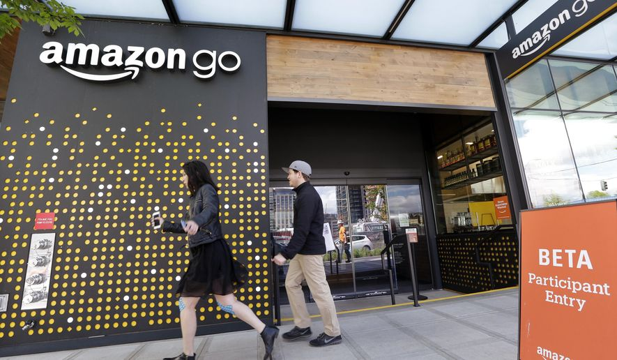 FILE - In this Thursday, April 27, 2017, file photo, people walk past an Amazon Go store in Seattle. More than a year after it introduced the concept, Amazon is opening its artificial intelligence-powered Amazon Go store in downtown Seattle on Monday, Jan. 22, 2018. (AP Photo/Elaine Thompson, File)