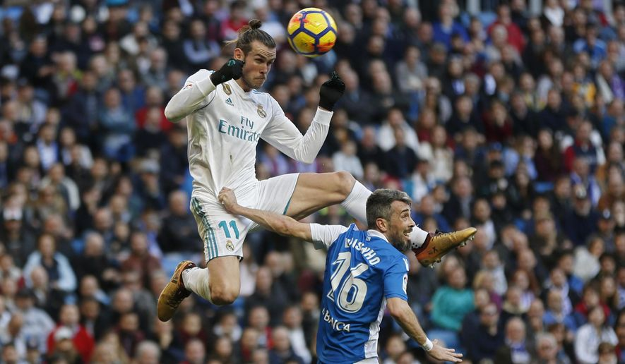 Real Madrid's Gareth Bale, top, out jumps Deportivo Coruna's Luisinho during a Spanish La Liga soccer match between Real Madrid and Deportivo Coruna at the Santiago Bernabeu stadium in Madrid, Sunday, Jan. 21, 2018. (AP Photo/Francisco Seco)