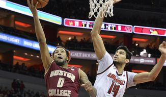 Boston College guard Ky Bowman (0) attempts a layup past the defense of Louisville forward Anas Mahmoud (14) during the first half of an NCAA college basketball game, Sunday, Jan. 21, 2018, in Louisville, Ky. (AP Photo/Timothy D. Easley)