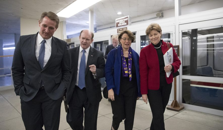 From left, Sen. Jeff Flake, R-Ariz., Sen. Chris Coons, D-Del., Sen. Amy Klobuchar, D-Minn., and Sen. Jeanne Shaheen, D-N.H., arrive at the Capitol after a bipartisan group of moderate senators held a private meeting on Day 2 of the federal shutdown, at the Capitol in Washington, Sunday, Jan. 21, 2018. Sen. Angus King, I-Vt., is seen at rear. (AP Photo/J. Scott Applewhite)