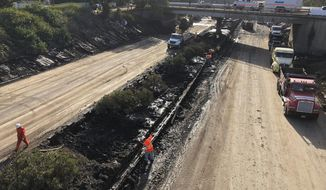 In this Wednesday, Jan. 17, 2018 photo Caltrans workers clear mud from a section of center divider guardrail along the northbound US 101 in Montecito in Montecito, Calif., that was closed following flooding on Jan. 9. California officials say key coastal highway swamped by deadly mudslides has reopened Sunday, Jan 21, 2018, after nearly 2-week closure. (Mike Eliason/Santa Barbara County Fire Department via AP, File)