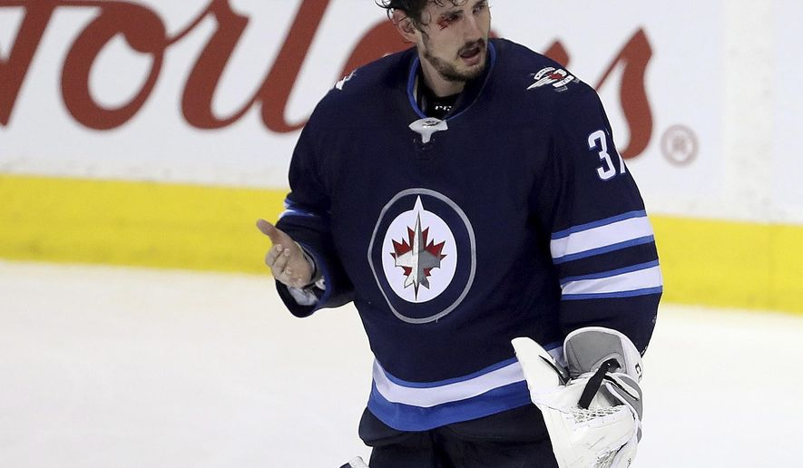Winnipeg Jets goalie Connor Hellebuyck reacts after getting a stick to the eye from teammate Josh Morrissey on a play in front of the net during the third period of the team's NHL hockey game against the Vancouver Canucks in Winnipeg, Manitoba, Sunday, Jan. 21, 2018. (Trevor Hagan/The Canadian Press via AP)