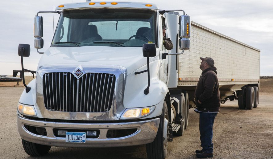 In this Dec. 21, 2017 photo, Bob Worth's son, John Worth, right, talks with another employee on the family farm while loading trucks with corn just outside of Lake Benton, Minn. Worth, whose family has farmed in western Minnesota for generations, is familiar with the pressures that can make modern farming stressful. (Evan Frost/Minnesota Public Radio via AP)