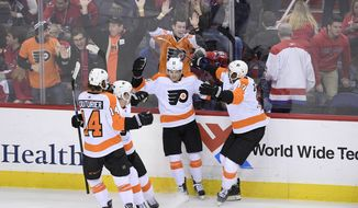 Philadelphia Flyers center Travis Konecny (11) celebrates his game-winning overtime goal with right wing Wayne Simmonds (17), center Sean Couturier (14) and defenseman Ivan Provorov, second from left, in an NHL hockey game against the Washington Capitals, Sunday, Jan. 21, 2018, in Washington. The Flyers won 2-1 in overtime. (AP Photo/Nick Wass)