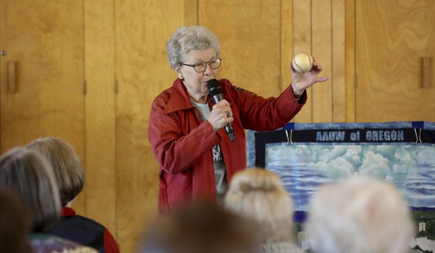 """Lois Youngen, of Eugene, shows the 10 inch baseball that she used while addressing an audience at the Westminster Presbyterian Church in Eugene, Ore. on Saturday, Jan. 13, 2018. Youngen was one of the 550 women who played professional baseball for 4 years after WWII. Their story was told in the film """"A League of Their Own."""" (Collin Andrew/The Register-Guard via AP)"""