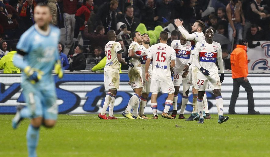 Lyon' players celebrate after Memphis Depay scored his side's second goal during the French League One soccer match between Lyon and Paris Saint Germain in Decines, near Lyon, central France, Sunday, Jan. 21, 2018. (AP Photo/Laurent Cipriani)