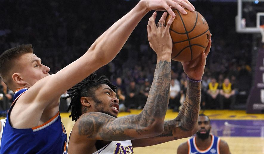 Los Angeles Lakers forward Brandon Ingram, right, has his shot blocked by New York Knicks forward Kristaps Porzingis, of Latvia, during the first half on an NBA basketball game, Sunday, Jan. 21, 2018, in Los Angeles. (AP Photo/Mark J. Terrill)