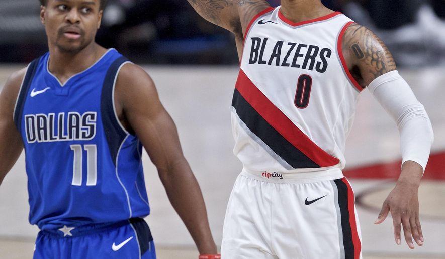 Portland Trail Blazers guard Damian Lillard, right, reacts after making a 3-point basket over Dallas Mavericks guard Yogi Ferrell during the second half of an NBA basketball game in Portland, Ore., Saturday, Jan. 20, 2018. (AP Photo/Craig Mitchelldyer)