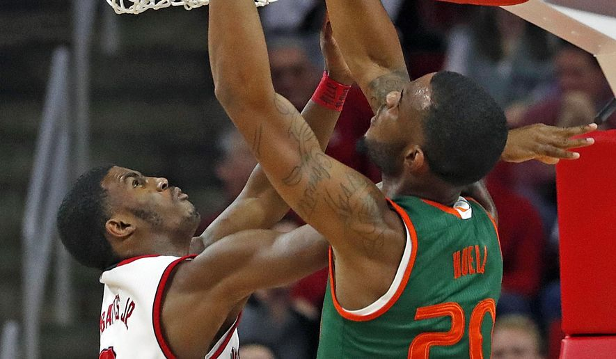 Miami's Dewan Huell (20) dunks the ball over North Carolina State's Lavar Batts Jr. (3) during the first half of an NCAA college basketball game in Raleigh, N.C., Sunday, Jan. 21, 2018. (AP Photo/Karl B DeBlaker)