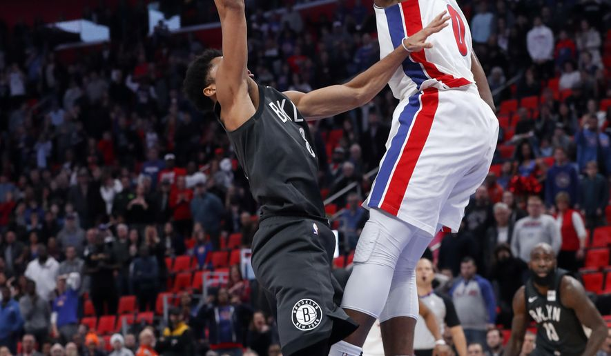 Brooklyn Nets guard Spencer Dinwiddie (8) hits the game winning shot over the defense of Detroit Pistons center Andre Drummond (0) in the second half of an NBA basketball game in Detroit, Sunday, Jan. 21, 2018. Brooklyn won 101-100. (AP Photo/Paul Sancya)