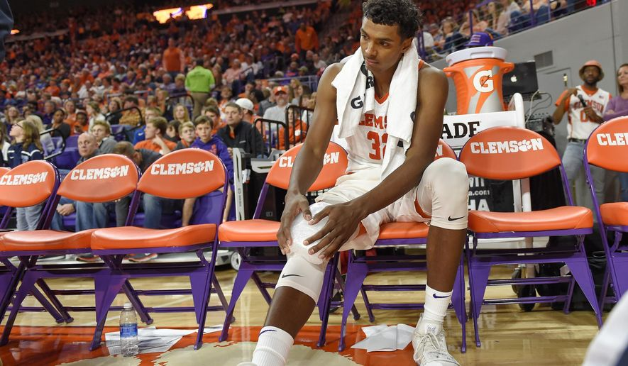 Clemson's Donte Grantham holds his knee after an injury during the second half of an NCAA college basketball game against Notre Dame Saturday, Jan. 20, 2018, in Clemson, S.C. Clemson won 67-58. (AP Photo/Richard Shiro)