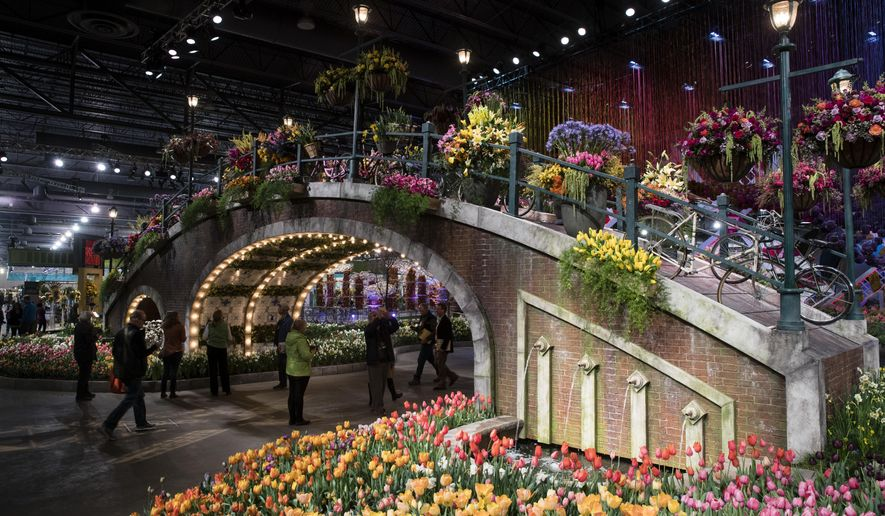 "FILE - In this March 10, 2017, file photo, visitors view horticultural displays during a preview of the annual Philadelphia Flower Show, featuring the theme ""Holland: Flowering the World,"" at the Pennsylvania Convention Center in Philadelphia. As the East Coast slogs through chilly temperatures and winter dreariness, visitors will dive into spring during the annual Philadelphia Flower Show from March 3 to 11, 2018, featuring the theme ""Wonders of Water"" and promising to ""celebrate the beauty and life-sustaining interplay of horticulture and water."" (AP Photo/Matt Rourke, File)"