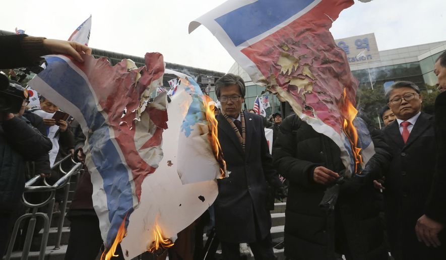 South Korean protesters burn a North Korean and Unification flag during a rally against a visit of North Korean Hyon Song Wol, head of a North Korean art troupe, in front of Seoul Railway Station in Seoul, South Korea, Monday, Jan. 22, 2018. The head of a hugely popular North Korean girl band crossed the heavily fortified border into South Korea on Sunday as part of an official delegation, triggering a media frenzy as she checked potential venues for performances during next month's Winter Olympics. (AP Photo/Ahn Young-joon)