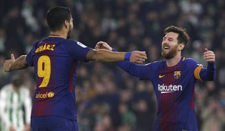 Barcelona's Messi, right, celebrates with teammate Suarez after scoring against Betis during the La Liga soccer match between Barcelona and Betis at the Villamarin stadium, in Seville, Spain on Sunday, Jan. 21, 2018. (AP Photo/Miguel Morenatti)