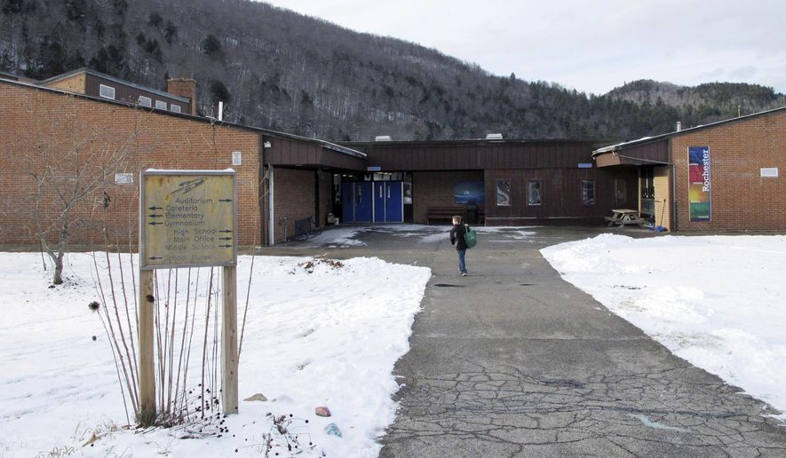 In this Dec. 11, 2017 photo, a student walks toward the Rochester School in Rochester, Vt. The middle-high school is slated to close at the end of the 2018 school year, as Rochester is among some small rural communities struggling to keep schools open in the face of dropping enrollment, rising costs and tightening budgets. (AP Photo/Lisa Rathke)