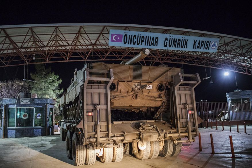 Turkish military trucks carrying tanks and other armoured vehicles cross through a border gate into a Turkish-controlled region of the Oncupinar border crossing with Syria, known as Bab al Salameh in Arabic, near the city of Kilis, Turkey, late Saturday, Jan. 20, 2018. The deployment occurred hours after dozens of Turkish jets bombed Syrian Kurdish militia targets in the enclave of Afrin. (Can Erok/DHA-Depo Photos via AP)