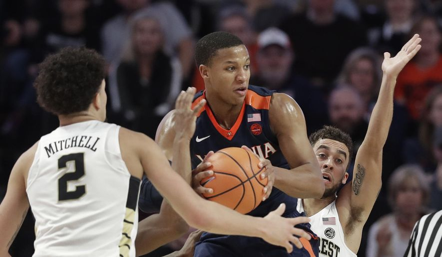 Virginia's Devon Hall, center, looks to pass as Wake Forest's Mitchell Wilbekin, back, and Donovan Mitchell, front, defend during the first half of an NCAA basketball game in Winston-Salem, N.C., Sunday, Jan. 21, 2018. (AP Photo/Chuck Burton)