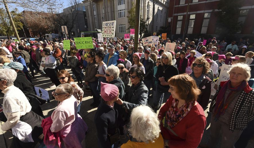 People hold signs during the Women's March in Wilmington, N.C., Saturday, Jan. 20, 2018. (Ken Blevins/The Star-News via AP)