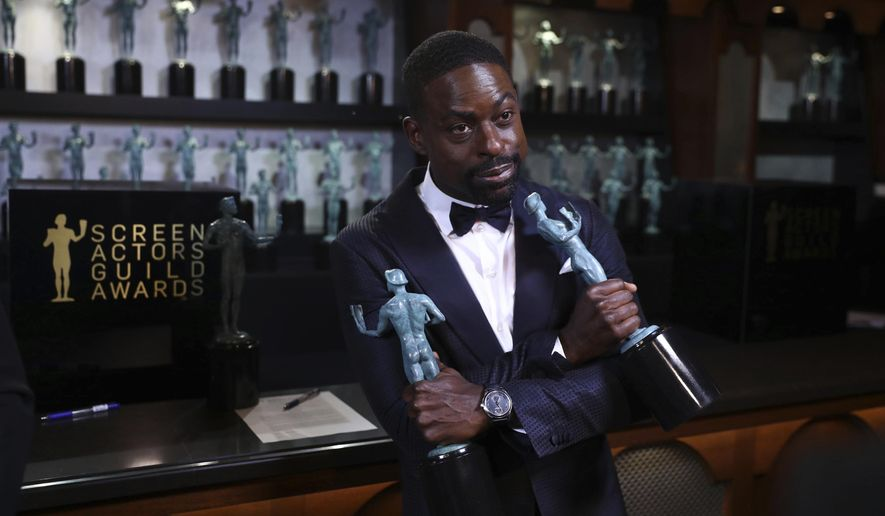 """Sterling K. Brown poses with his awards for outstanding performance by a male actor in a drama series for """"This Is Us"""" and for outstanding performance by an ensemble in a drama series for """"This Is Us"""" backstage at the 24th annual Screen Actors Guild Awards at the Shrine Auditorium & Expo Hall on Sunday, Jan. 21, 2018, in Los Angeles. (Photo by Matt Sayles/Invision/AP)"""