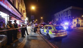 """This is a June 19, 2017 file photo  of a police cordon at attack near Finsbury Park Mosque in north London. British prosecutors Monday Jan. 22, 2018  described the suspect in the June attack near London's Finsbury Park Mosque as a """"ticking time bomb"""" who became convinced that all Muslims were extremists or rapists in pedophile gangs after watching a television show on child exploitation in north-central England. The allegations came during the trial Monday of 48-year-old Darren Osborne, who is accused driving his van into a crowd of worshippers attending Ramadan prayers.  (Yui Mok/PA, File via AP)"""