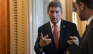 Sen. Joe Manchin, D-W.Va., talks with a staffer on Capitol Hill in Washington, Monday, Jan. 22, 2018, after passage of a procedural vote aimed at reopening the government. (AP Photo/Susan Walsh)