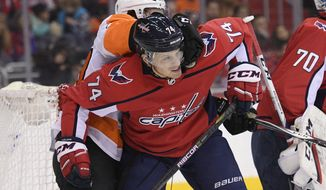 Washington Capitals defenseman John Carlson (74) battles for position against Philadelphia Flyers center Jordan Weal, back, during the first period of an NHL hockey game, Sunday, Jan. 21, 2018, in Washington. (AP Photo/Nick Wass)