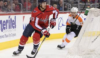 Washington Capitals center Jay Beagle (83) skates with the puck in front of Philadelphia Flyers center Scott Laughton (21) during the first period of an NHL hockey game, Sunday, Jan. 21, 2018, in Washington. (AP Photo/Nick Wass)