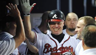 FILE - In this Aug. 16, 2012, file photo, Atlanta Braves' Chipper Jones celebrates with teammates after scoring a home run on his 2700th career hit in the fifth inning of a baseball game against the San Diego Padres, in Atlanta. All signs point to Jones being selected to the Baseball Hall of Fame when the next group of inductees is announced Wednesday, Jan. 24, 2018. (AP Photo/Rainier Ehrhardt, File) **FILE**