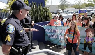 Maria Bilbao, right, talks with a Doral police officer outside of the office of Sen. Marco Rubio, R-Fla., as protesters march in support of Deferred Action for Childhood Arrivals (DACA), and Congress passing a clean Dream Act, Monday, Jan. 22, 2018, in Doral, Fla. They weren't permitted to enter the office due to the government shutdown. (AP Photo/Lynne Sladky)