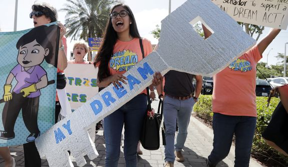 "Maria Angelica Ramirez carries a large key reading ""My Dream"" during a protest outside the office of Sen. Marco Rubio, R-Fla., in support of Deferred Action for Childhood Arrivals (DACA), and Congress passing a clean Dream Act, Monday, Jan. 22, 2018, in Doral, Fla. (AP Photo/Lynne Sladky)"