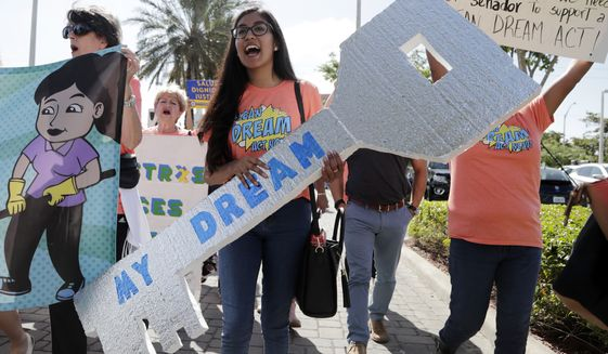 "Maria Angelica Ramirez carries a large key reading ""My Dream"" during a protest outside the office of Sen. Marco Rubio, Florida Republican, in support of Deferred Action for Childhood Arrivals. (Associated Press)"