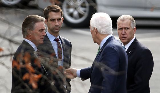 From left, Sen. David Perdue, R-Ga., Sen. Tom Cotton, R-Ark., Sen. John Cornyn, R-Texas, and Sen. Thom Tillis, R-N.C., gather to wait for their vehicles as they leave the White House in Washington, Monday, Jan. 22, 2018. (AP Photo/Carolyn Kaster)