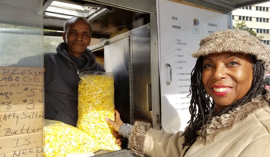 Michael Habteselasse sells a bag of popcorn from his truck near L'Enfant Plaza on Monday during the federal government shutdown. Mr. Habteselasse, 62, said he made only about a third of his usual sales on Monday. (Julia Airey / The Washington Times)