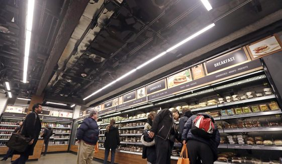 Sensors and cameras, part of a system used to tell what people have purchased, are attached overhead as shoppers walk below, in an Amazon Go store, Monday, Jan. 22, 2018, in Seattle. The artificial intelligence-powered store, which opened to the public Monday, allows shoppers to scan their smartphone with the Amazon Go app at a turnstile, pick out the items they want and leave. The online retail giant can tell what people have purchased and automatically charges their Amazon account. (AP Photo/Elaine Thompson)