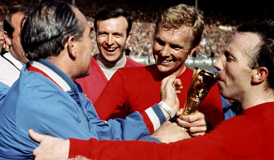 FILE - This is a July 30 1966 file photo of of England manager Alf Ramsey left, as he is congratulated by England squad member Jimmy Armfield, 2nd left,  with players Nobby Stiles, right, and captain Bobby Moore, after England won World Cup  final against  West Germany at Wembley Stadium in London. Jimmy Armfield, a former England captain who led Leeds to the European Cup final as a manager before a distinguished career in broadcasting, has died on monday Jan. 22, 2018. He was 82. (Ron Bell/PA File via AP)