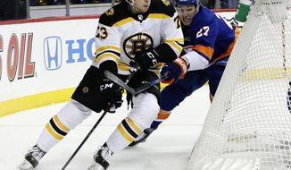 Boston Bruins' Charlie McAvoy (73) is defended by New York Islanders' Anders Lee (27) during the first period of an NHL hockey game Thursday, Jan. 18, 2018, in New York. (AP Photo/Frank Franklin II)