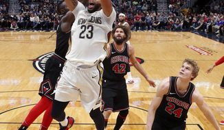 New Orleans Pelicans forward Anthony Davis (23) goes to the basket in front of Chicago Bulls center Robin Lopez (42) and forward Lauri Markkanen (24) in the first half of an NBA basketball game against the Chicago Bulls in New Orleans, Monday, Jan. 22, 2018. (AP Photo/Gerald Herbert)