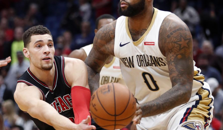 Chicago Bulls guard Zach LaVine (8) passes around New Orleans Pelicans center DeMarcus Cousins (0) in the first half of an NBA basketball game in New Orleans, Monday, Jan. 22, 2018. (AP Photo/Gerald Herbert)