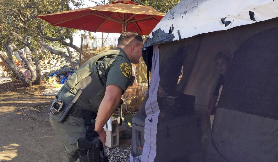 An Orange County sheriff's deputy calls to residents inside a tent in Anaheim, Calif., Monday, Jan. 22, 2018, to let them know they'll need to leave the area and that the county will assist with the move if they need. Southern California authorities on Monday went tent to tent telling the homeless they're shutting down the large riverbed encampment some have called home for years. (AP Photo/Amy Taxin)